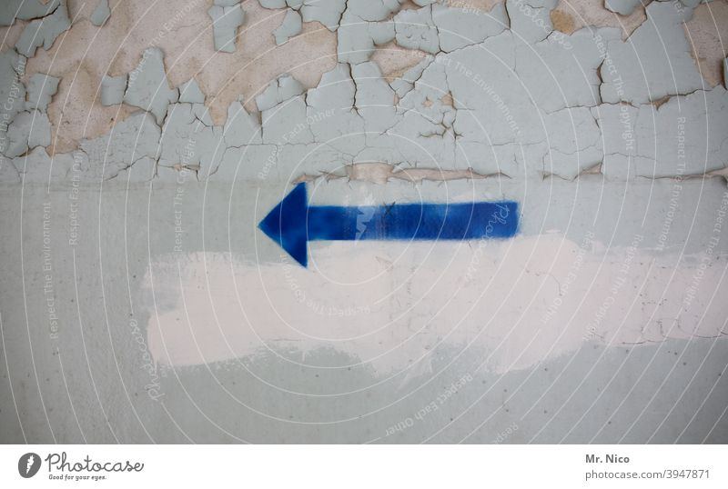 blue arrow on wall Arrow Direction Trend-setting Orientation Sign Target to the left Wall (building) Blue Flake off Wall (barrier) Gray Redecorate Dirty