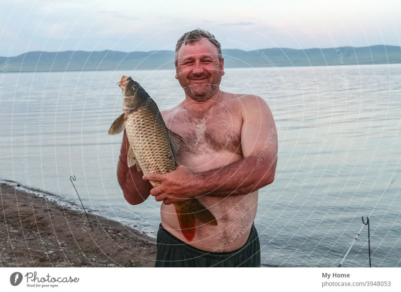 Stocky man with big carp. Khakassia, Russia autumn background beach beautiful blue camp catch fish fisherman fishing gold happy hobby lucky nature outdoor