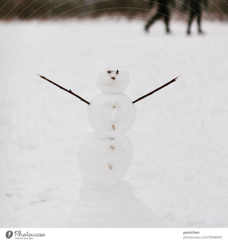 A snowman with outstretched arms stands in the snow. Blurred walkers in the background. Winter Snowman Children's game Joy fun pleasure Cold strollers Seasons