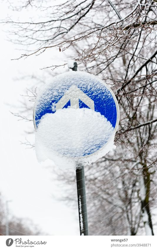 Traffic sign prescribed driving direction straight ahead (traffic sign no. 209-30) partly covered with snow Road sign direction of travel