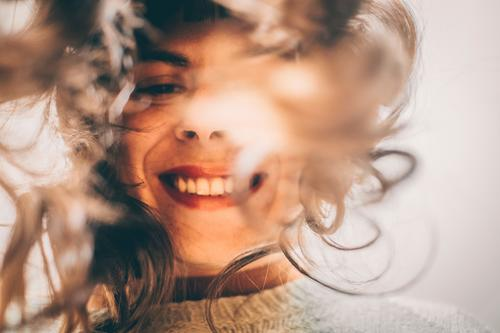 Woman with long hair looks into camera bent over and smiles Smiling Selfie long hairs Laughter Good mood Joy look in leaning over Authentic Happiness