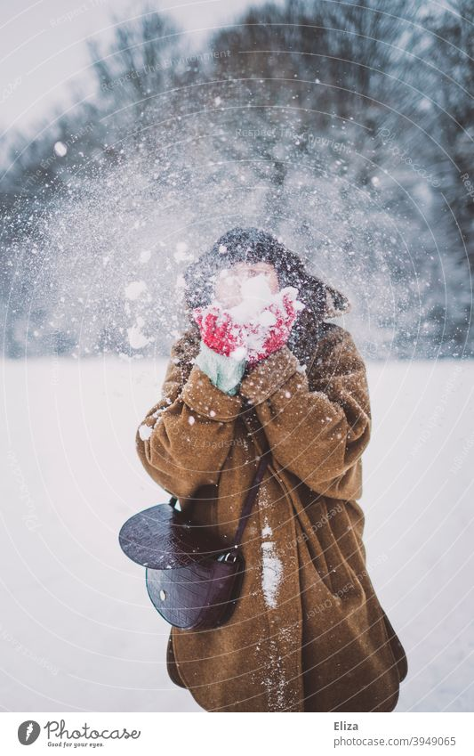 A woman with a cloud of snow in front of her face Snow snow cloud blow winter Winter Woman youthful snow flurries Snowscape Nature Winter mood Winter's day Cold