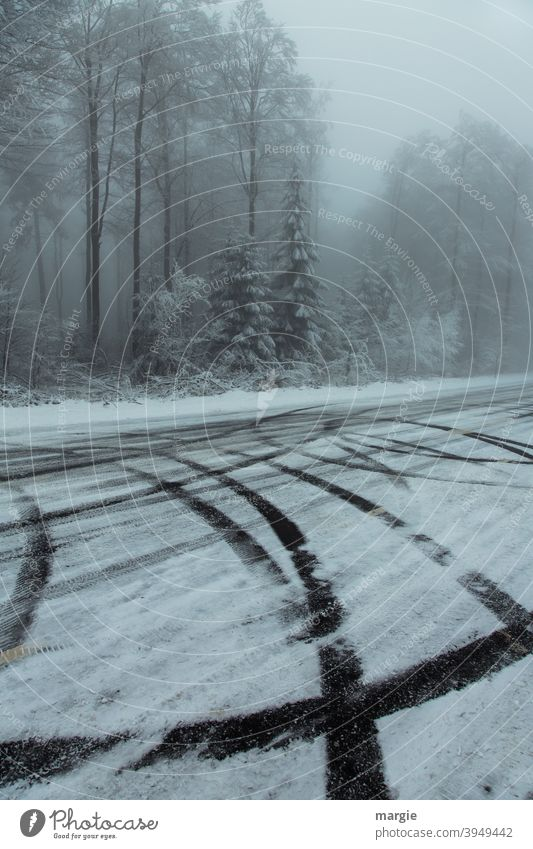 a wintry forest with tire tracks on a slippery road with snow and ice Winter Black ice ice and snow Ice and frost Tracks Skid marks trees Nature Landscape