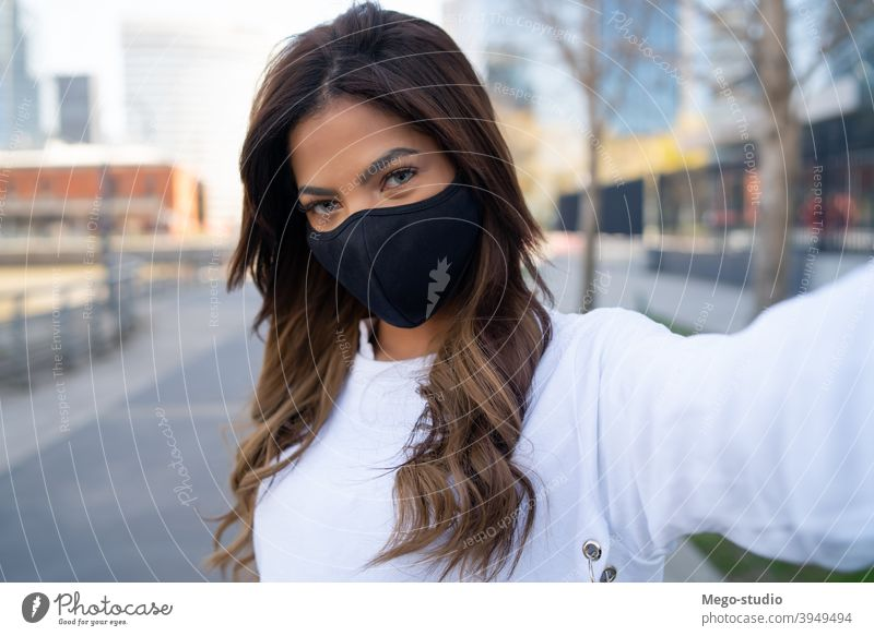 Young woman taking selfies outdoors. young urban face mask portrait lifestyle travel street brunette vacation tourist modern picture photographing posing