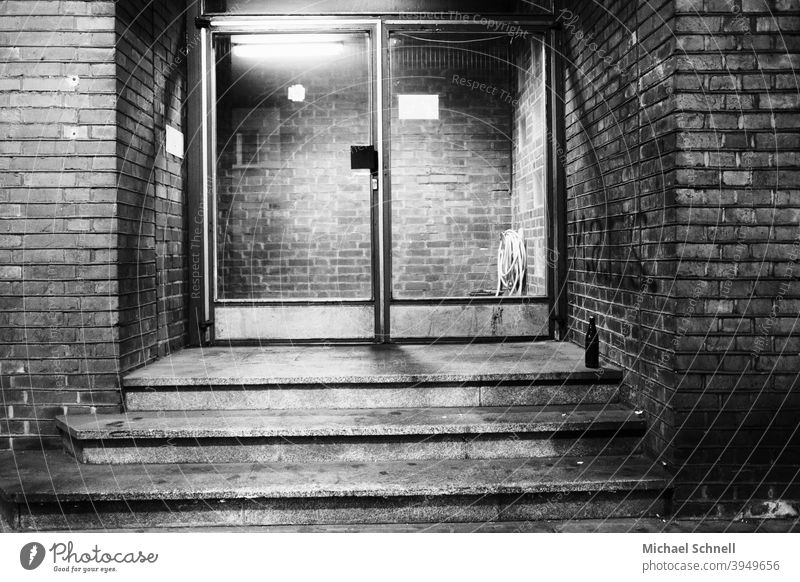 Entrance glass door of a brick office building with a beer bottle in front of it Glass door Front door Deserted Exterior shot House (Residential Structure)