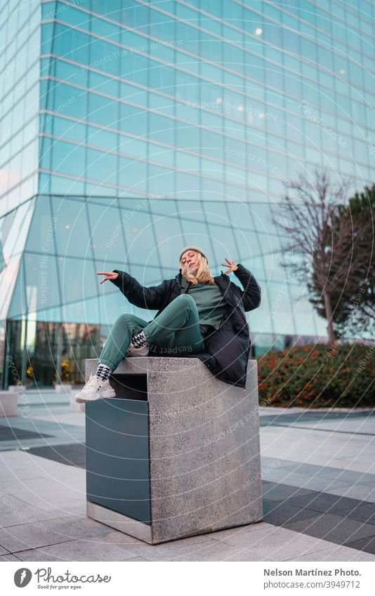 Blonde woman in a green outfit, a gray wool hat and a black jacket with a building in the background fashion portrait cold wear cute outdoor pretty apparel
