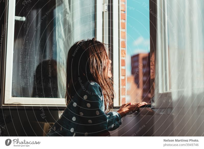 Beautiful shot of a little girl with dark hair looking out the window on a sunny day. Sun Sunlight Portrait Child Girl Childhood portrait child kid cute Infancy