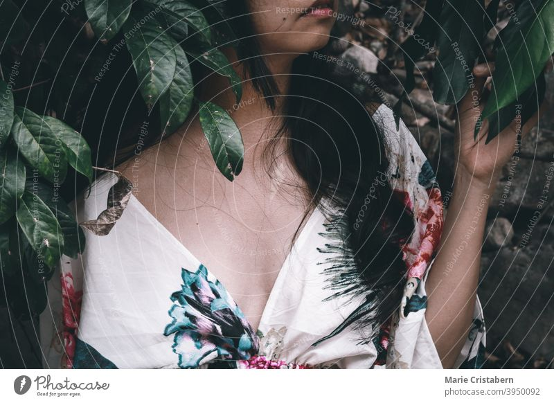 Portrait of a woman in floral dress against tropical leaves summer spring portrait outdoor feminine moody pink contentment youth hairstyle summertime skincare