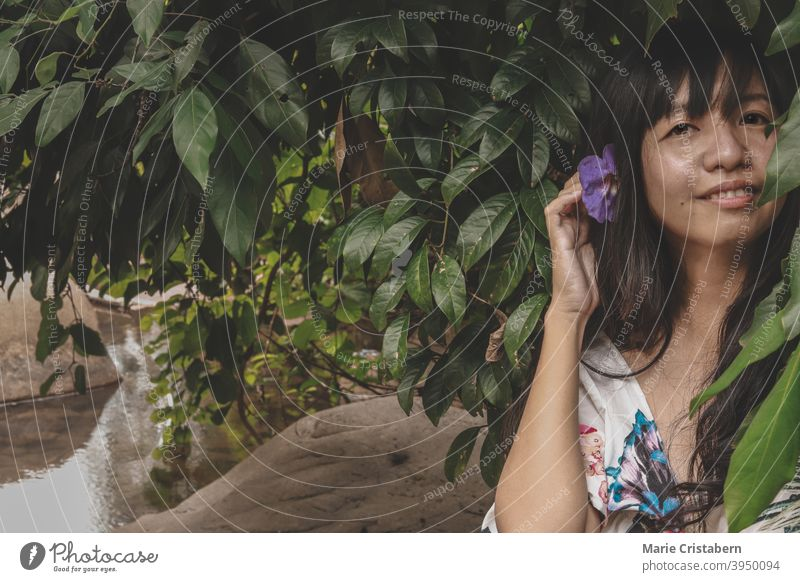 Beautiful woman with flower in her hair against the dark tropical foliage showing concept of Springtime and Summer outdoor person enjoy fun elegant casual