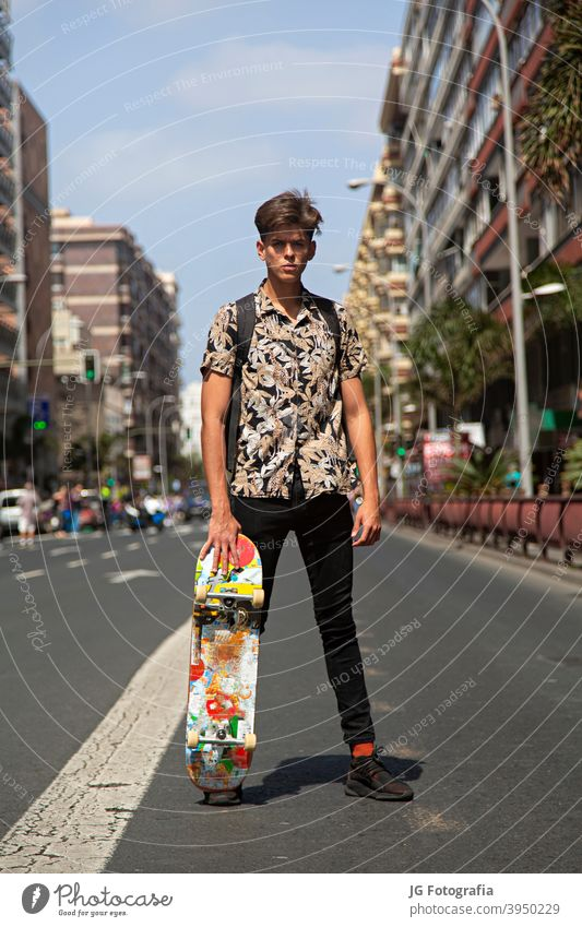 Portrait of young skateboarder man with bad boy face in the middle of the street. portrait guy urban model fashion retro attitude look gaze poster frontal