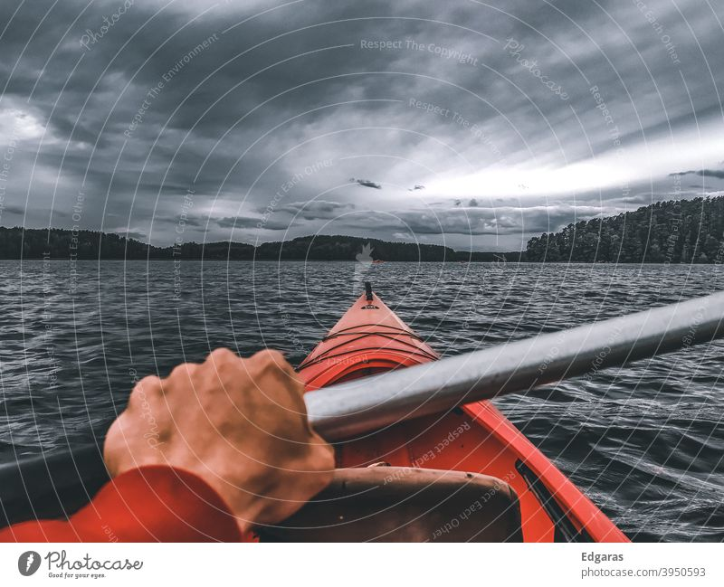 Man hand kayaking in a river, stormy day Kayak kayaker Kayaks Hand Adventure Travel Water Storm Clouds River Lake Red Vacation & Travel canoe Canoe trip