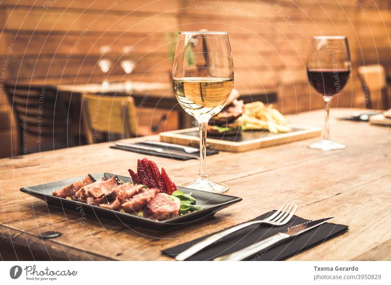 Traditional restaurant atmosphere with tuna tataki and burger with chips in the background on rustic wooden table and glass of white wine fish tomato cup