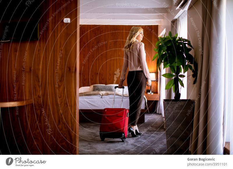 Young businesswoman arrives in a hotel room with red suitcase adult arrival bag bed bedroom caucasian charming elegance female holiday home indoor interior