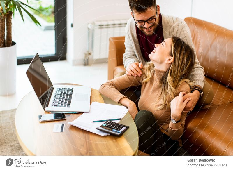 Young couple using laptop together while sitting on sofa at home woman internet happy computer indoors people caucasian couch house room young smiling lifestyle