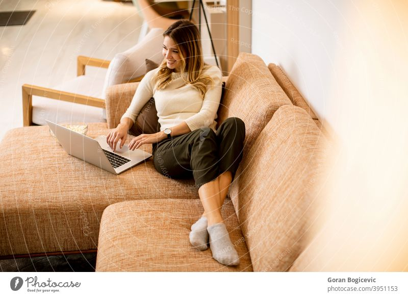 Young beautiful woman using a laptop at home sofa internet computer technology room beauty leisure pretty living lifestyle young couch female person happy
