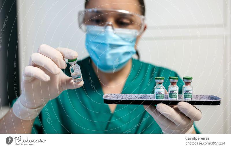 Female laboratory technician examining vial of coronavirus vaccine. pharmaceutical laboratory covid-19 tray medical medicine caution plate research drug