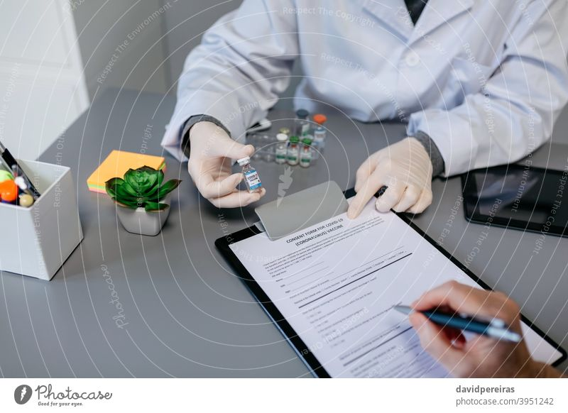 Unrecognizable doctor explaining to her patient the benefits and risks of the coronavirus vaccine consent form unrecognizable vial covid-19