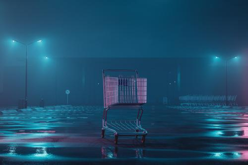 illuminated shopping cart on abandoned, foggy parking lot. Concept Lockdown Stands Outdoors Shopping center Mall Commerce Street Commercial Parking Metal