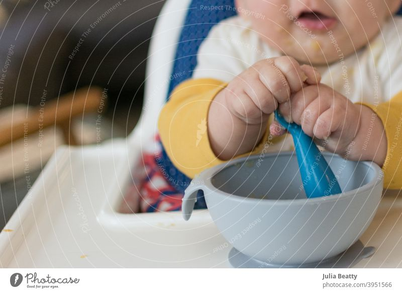 6 month old baby in high chair grasping spoon with two hands while self feeding baby led weaning first foods apple apple sauce finger foods hold child eating
