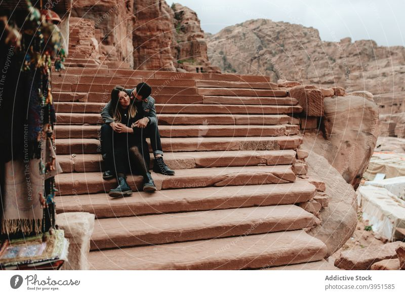 Romantic young ethnic couple embracing sitting on stairs hug romantic date love together relax relationship style rest tender close fondness boyfriend