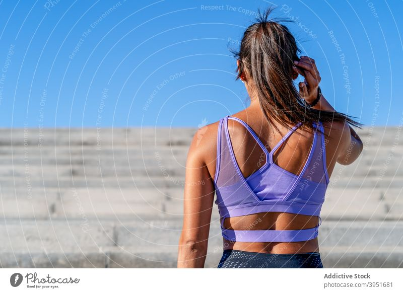 Fit woman in sportswear standing near stairs during training sportswoman fit slim workout summer city determine activewear athlete female vitality wellness
