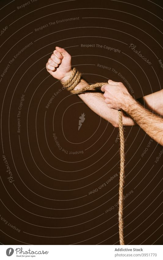 Crop man with rope on hand in studio untie free freedom slave concept strong confident tight male equipment motivation power strength clench fist muscular fit