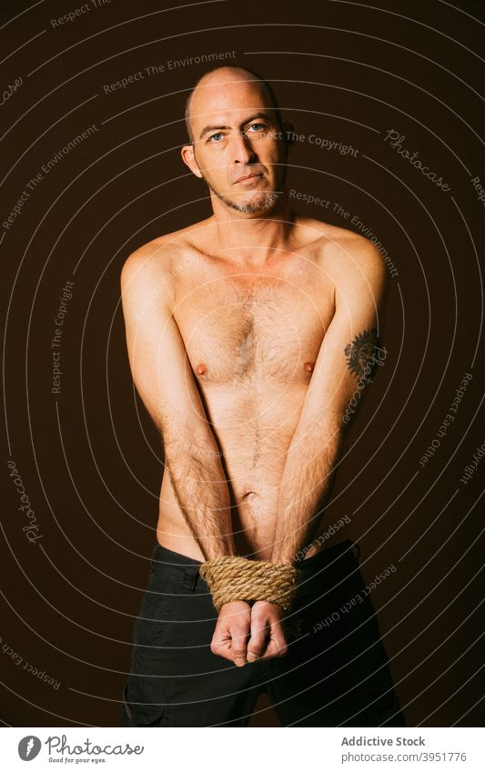 Man tied with rope standing in studio man naked torso shirtless calm serious figure sporty male handsome muscular body macho chest strong determine athlete guy