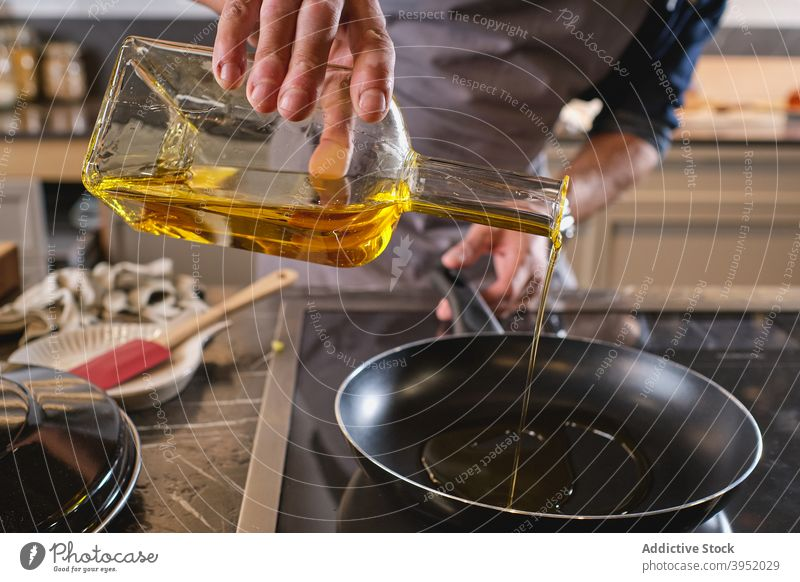 Unrecognizable man pouring oil into saucepan kitchen home add chef modern bottle male ingredient recipe middle age mature lunch dinner culinary cook glass beard