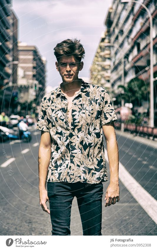Young man with tough guy face walking in the middle of the street. portrait young skateboarder urban model fashion retro attitude look gaze poster frontal