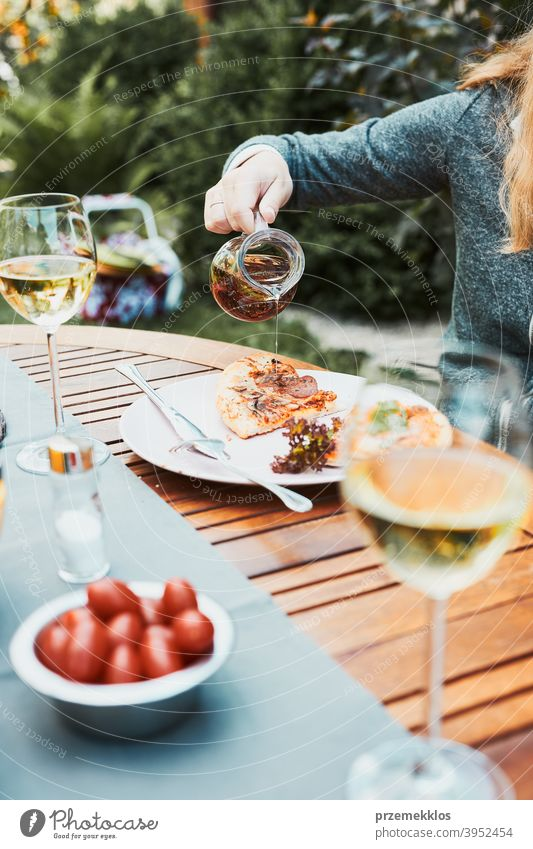 Family and friends having meal - pizza, salads, fruits and drinking white wine during summer picnic outdoor dinner in a home garden backyard beverage