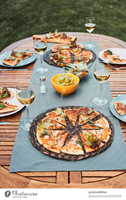 Dinner in a home garden. Pizza, salads, fruits and white wine on table in a backyard beverage celebration dinner dish drink eating feast food gathering having