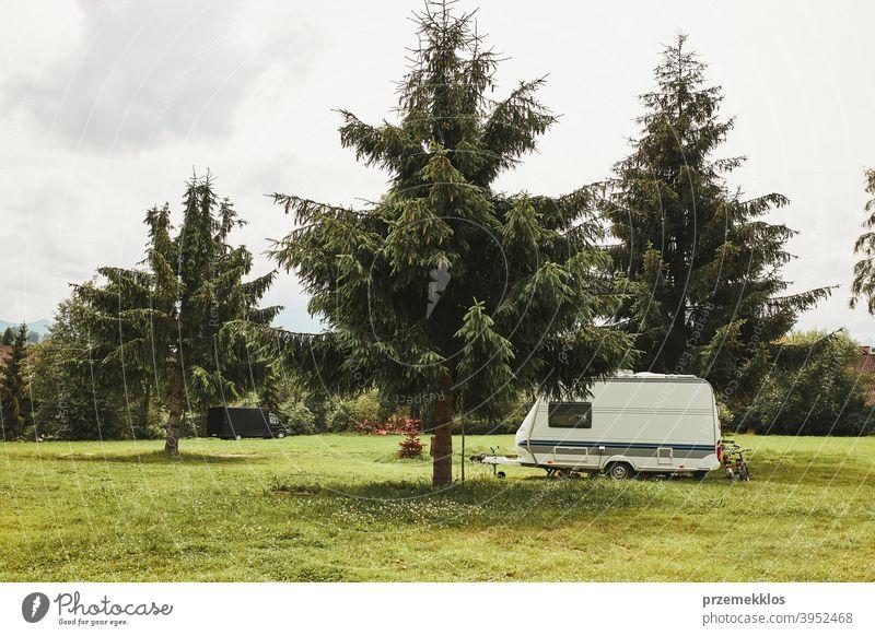 Caravan left among the pine trees on campsite exploring recreation house trip car transport grass ground field camping recreational equipment van life