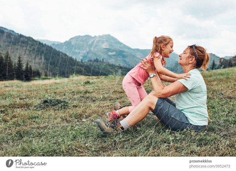 Little girl playing with her mother on grass enjoying summer day during vacation trip in mountains happy excitement enjoyment leisure emotion positive lifestyle