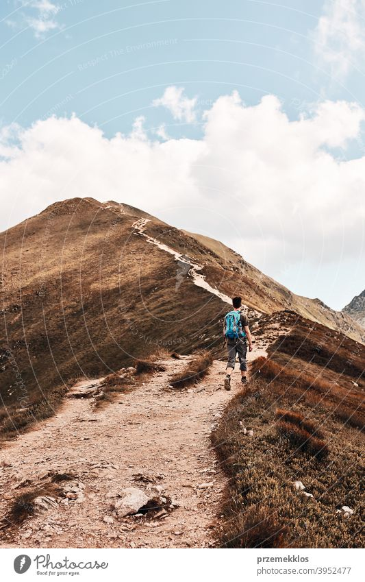 Young man with backpack hiking in a mountains, actively spending summer vacation activity adventure freedom healthy joy leisure nature park recreation spring