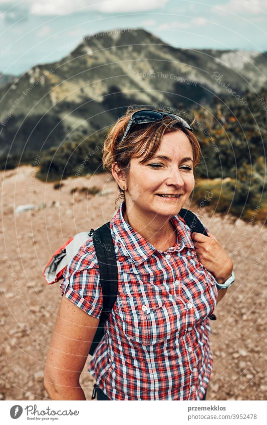 Smiling happy woman with backpack hiking in a mountains, actively spending summer vacation activity adventure female freedom fun green healthy joy leisure
