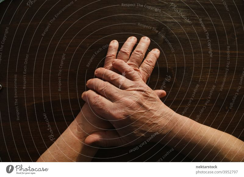 Hands and Arms of Old Man on Wooden Surface hand old finger male man arm high angle view unrecognizable person limb indoor professional lighting body part