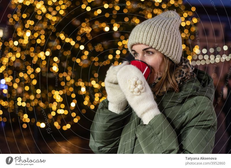 Woman drinking on Christmas market christmas woman cup holiday christmas market mulled wine hot drink winter outdoor person adult female december light cheerful