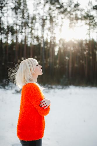 Cute girls have fun in the frozen park. Woman in a knitted sweater.the girl's hands froze winter portrait outdoor orange nature happy forest woman beautiful