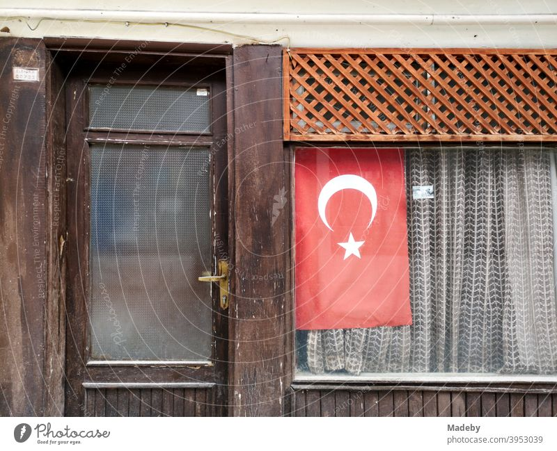 The Turkish flag in the window of a small old shop with curtain in Göynük in the province of Bolu in Turkey nationalism national pride national feeling