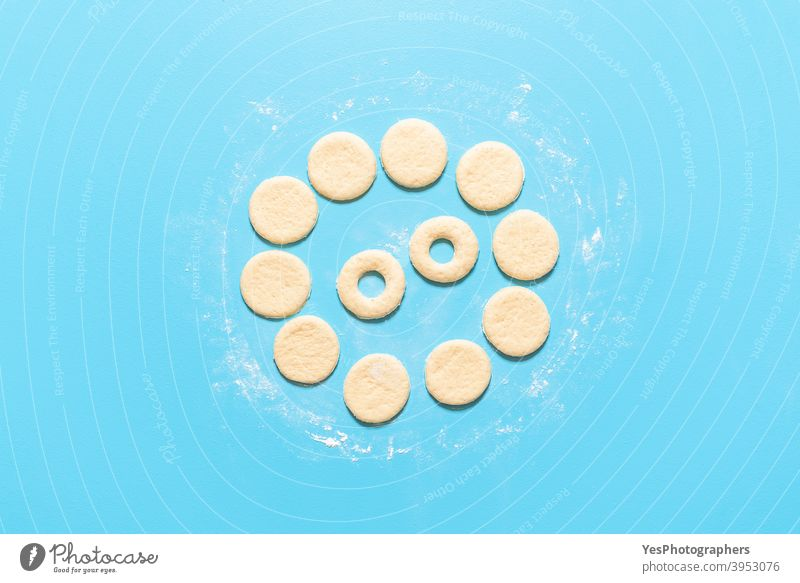 Making doughnuts flat lay. Uncooked raw dough prepared for donuts aligned american baking blue background breakfast cake calories circle shape comfort food