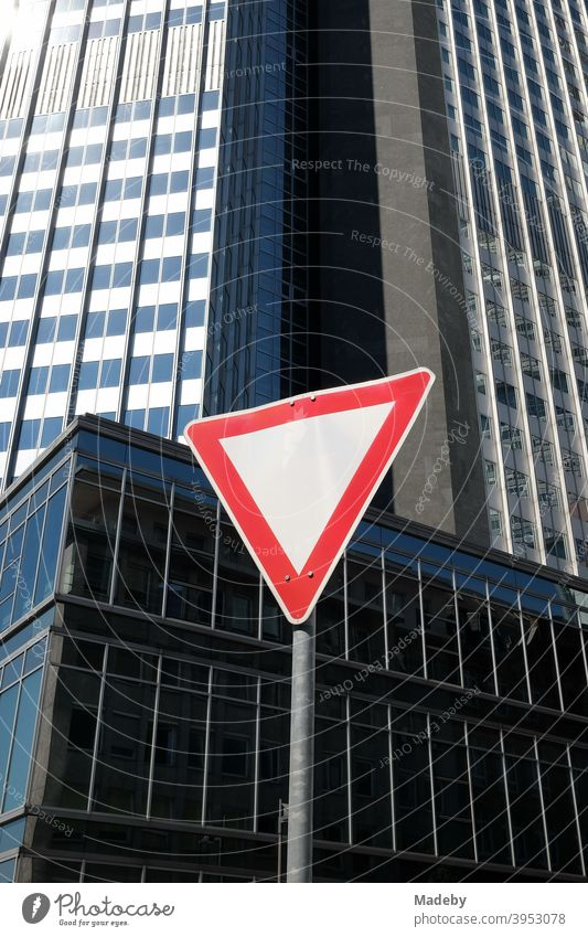 Triangular traffic sign grant right of way in the Neue Mainzer Straße in front of the Eurotower in summer at sunshine in Frankfurt am Main in Hesse Road sign