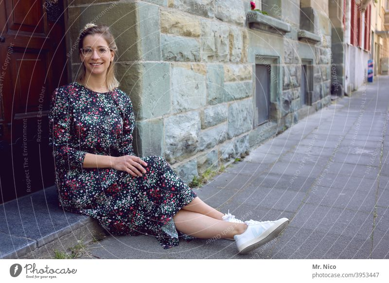 young woman sits in front of the house door and waits Sit Wait Facade Building Old town Front door Entrance House (Residential Structure) Summer dress Sidewalk