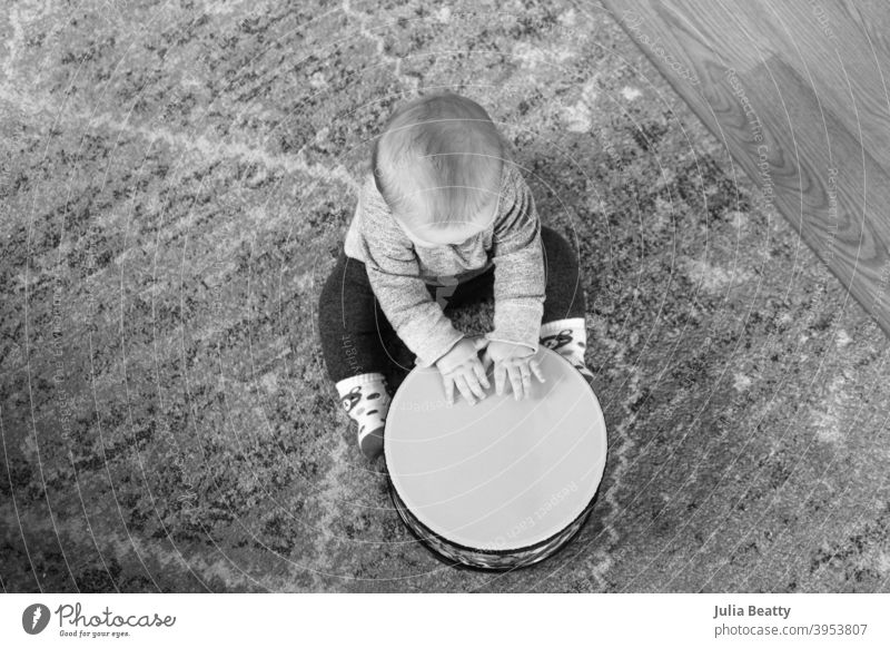 6 month old baby playing drum while seated on a rug on the floor; black and white image from bird's eye view floor drum 6 months old hands beat tap scratch