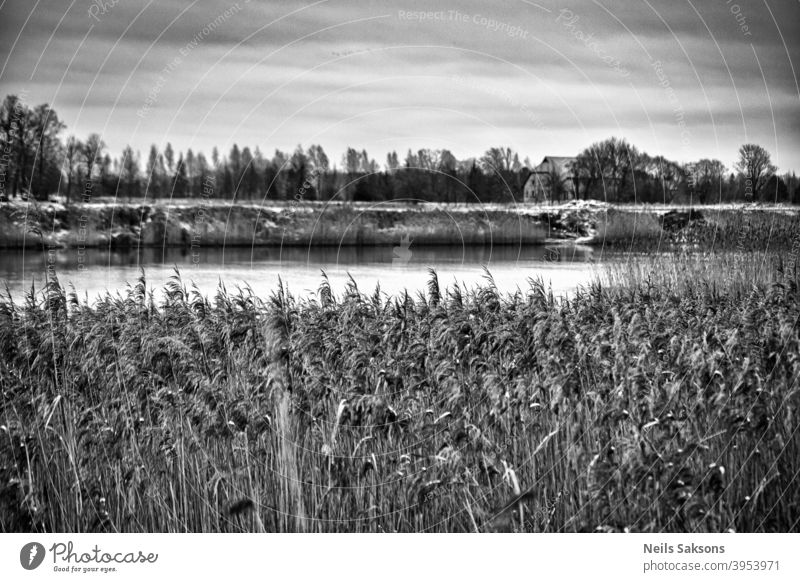 who lives on the other shore of river / over the reeds Latvia beautiful black and white building canal clouds coast coastal coastline country countryside day