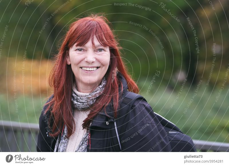 Happy smiling woman with red long hair outside in nature Looking into the camera Front view Upper body portrait Central perspective Shallow depth of field
