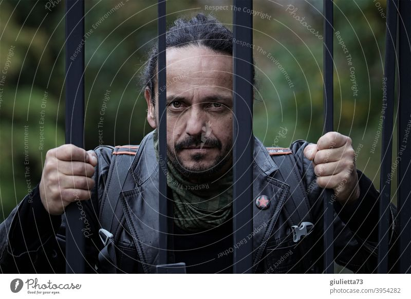 Angry man with fixed gaze behind wire fence, pursuer, stalker, scary, dangerous ostracized Emotions Leather jacket Man Adults 1 Human being 30 - 45 years