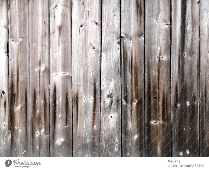 Beautiful brown old wood with grain and knotholes of a hut on a farm in Upper Bavaria Wood Facade board Rough Old Wood grain Knothole Craft (trade) Tradition
