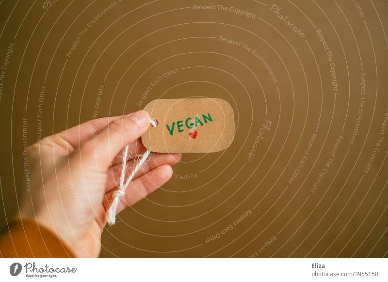 Hand holding a label with the word vegan written on it. Vegan lifestyle. vegan lifestyle vegan products Shopping Consumption Products Label commodities
