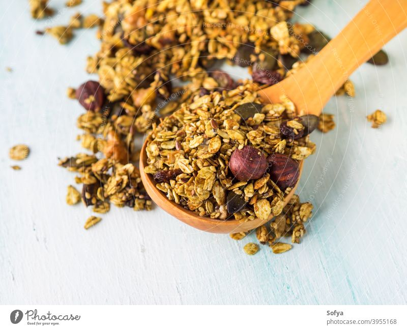 Matcha green tea granola with nuts and seeds homemade matcha bowl pastel turquoise background oats berries dried fruit sesame healthy plant based vegan