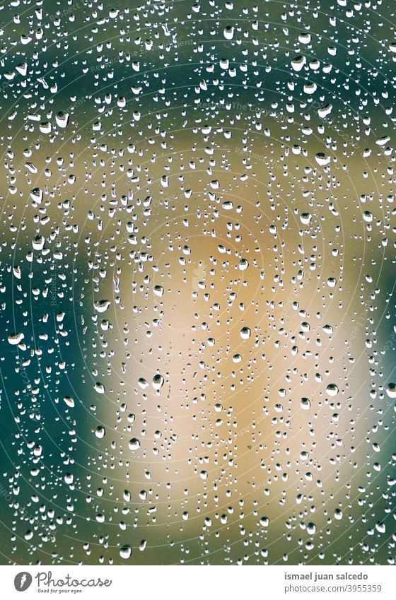 raindrops on the window in rainy days water wet abstract background textured lights colorful street outdoors colors bright winter